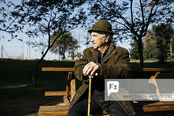 Old man with cane sitting on banch in a park