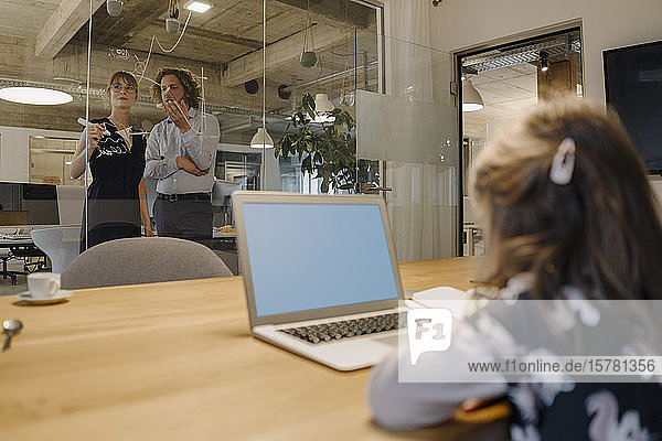 Businessman and businesswoman working on a project in office with girl using laptop in foreground