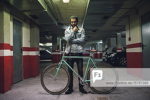 Junger Mann steht mit seinem Fixie-Rad im Parkhaus