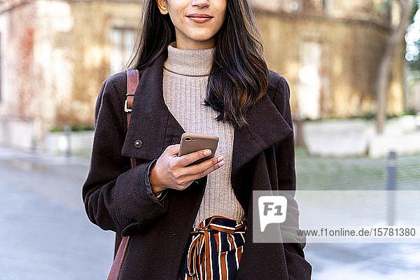 Nahaufnahme einer Frau mit einem Smartphone in der Stadt