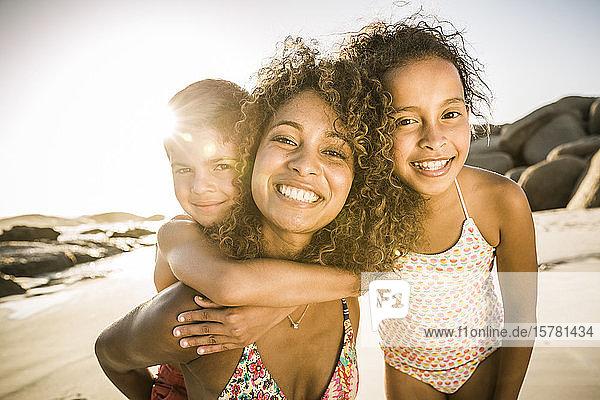 Porträt einer glücklichen Mutter mit ihren zwei Kindern  die sich am Strand amüsieren