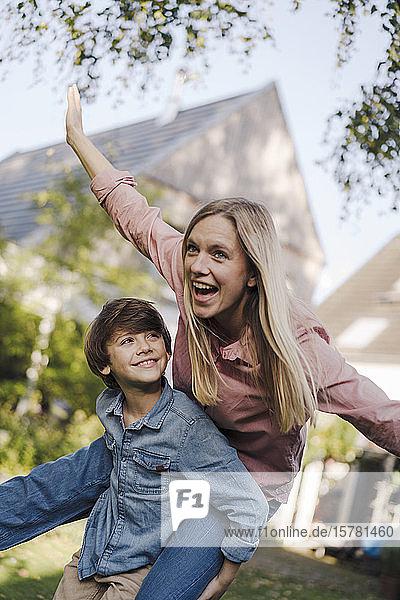 Mutter und Sohn amüsieren sich  spielen im Garten und tun so  als würden sie fliegen