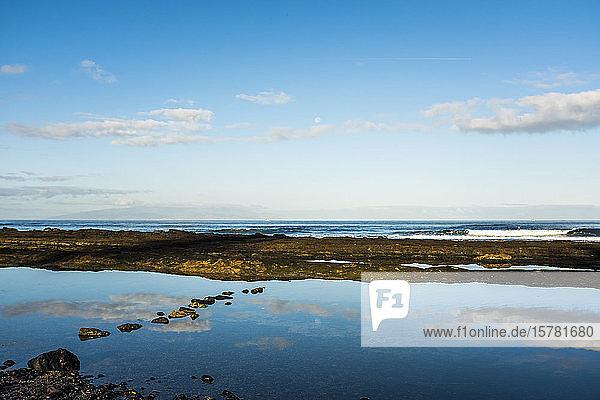 Spanien  Kanarische Inseln  Teneriffa  Wolken  die sich in großer Pfütze am Küstenstrand spiegeln