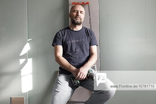 Porträt eines selbstbewussten Mannes  der eine tragbare Bohrmaschine auf einer Baustelle zu Hause hält