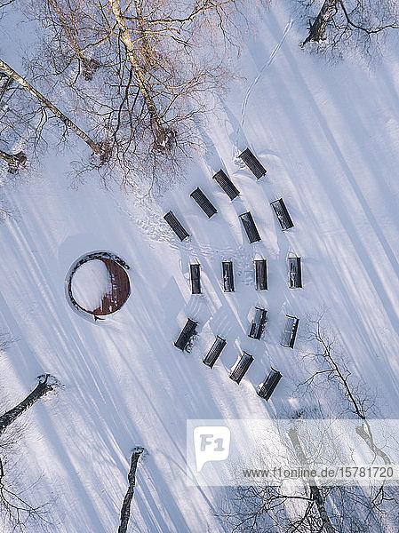 Leere Bänke im schneebedeckten Park  Drohnenansicht