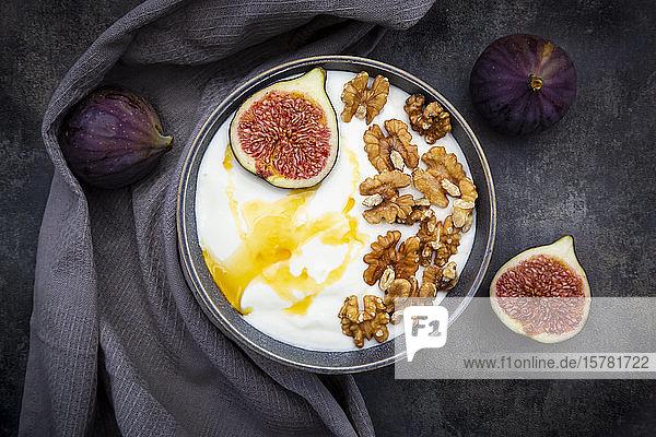 Schale mit griechischem Joghurt mit Honig  Walnüssen und geschnittener Feige