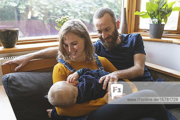Glückliche Familie auf dem Sofa mit schlafendem kleinen Sohn