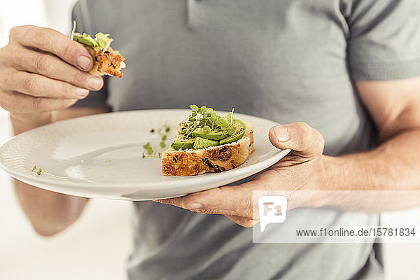 Close-up of man holding a plate with a healthy avocado bread