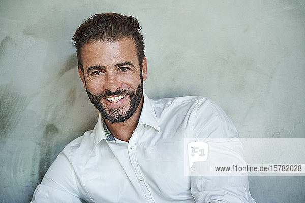 Portrait of happy businessman wearing white shirt