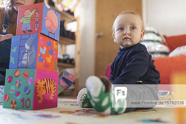 Kleiner Junge spielt zu Hause im Wohnzimmer