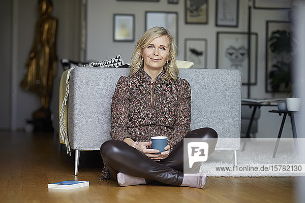 Blond woman relaxing at home sitting on the floor