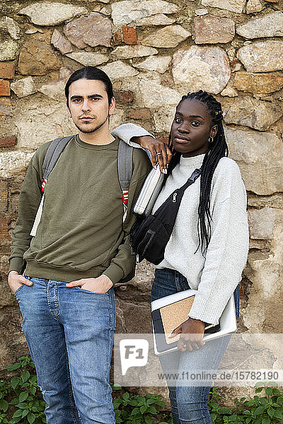 Portrait of a confident couple at a stone wall