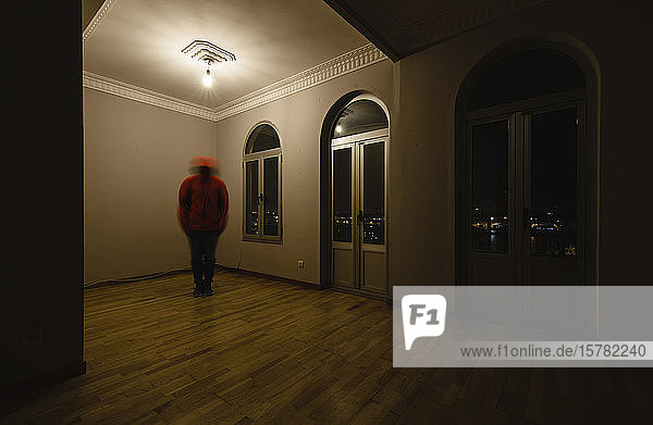 Trembling person standing in empty room at night