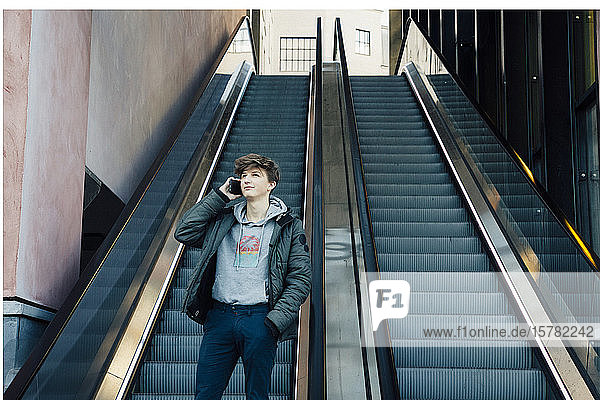 Teenager mit Smartphone vor einer Rolltreppe