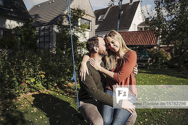 Liebespaar sitzt auf der Schaukel in seinem Garten