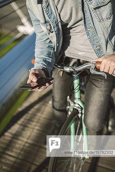 Junger Mann  der mit seinem Fixie-Rad durch die Stadt pendelt und ein Smartphone benutzt