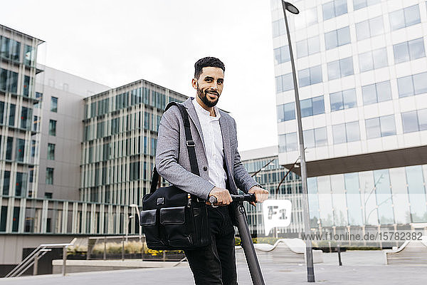 Portrait of casual young businessman with electric scooter in the city