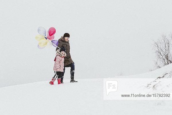 Mutter und kleines Mädchen mit Luftballons gehen in verschneiter Landschaft