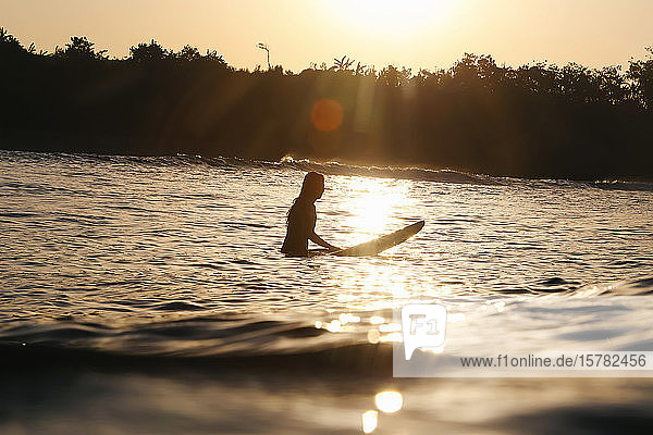 Female surfer at sunset  Bali  Indonesia