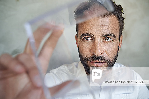 Portrait of businessman looking at transparant cube