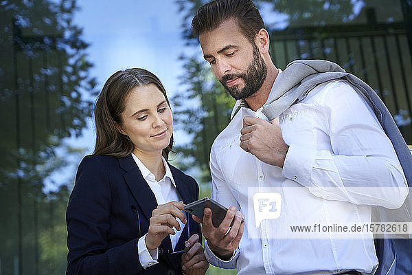 Businessman and businesswoman looking at cell phone in the city
