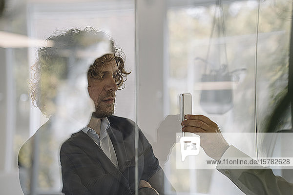 Businessman showing cell phone to colleague behind glass pane