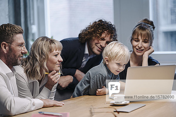 Business team with boy looking at laptop in office