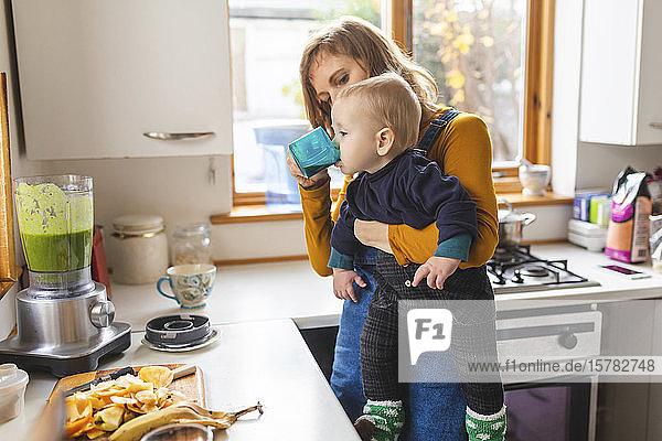 Frau in der Küche bereitet gesunden Smoothie zu und hält ihren kleinen Sohn