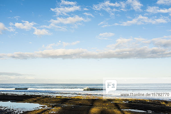 Spanien  Kanarische Inseln  Teneriffa  Himmel über dem Küstenstrand mit Surfern im Hintergrund