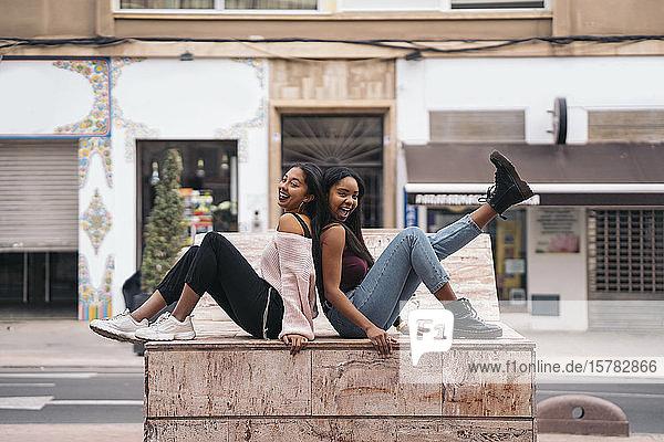 Zwei glückliche junge Frauen in der Stadt