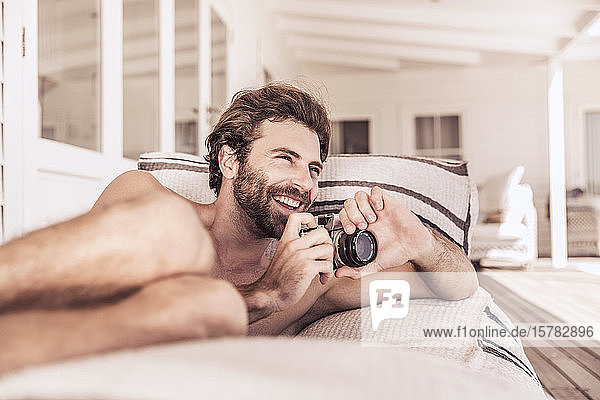 Happy young man with vintage camera relaxing on a veranda