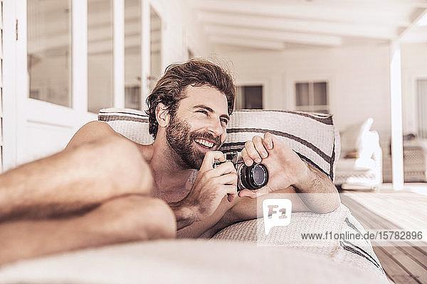 Fröhlicher junger Mann mit Oldtimer-Kamera entspannt auf einer Veranda