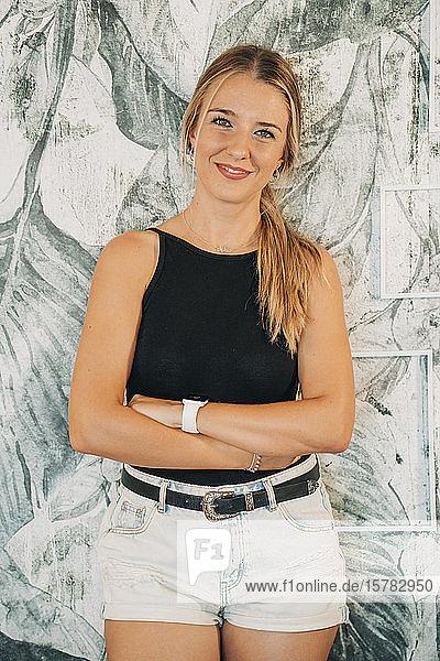 Porträt einer lächelnden Frau  die an einer Wand steht