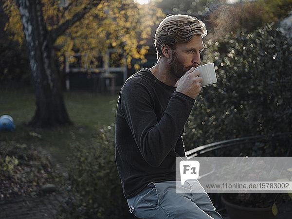 Mann bei einer Kaffeepause im Garten