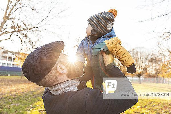 Mann hebt seinen kleinen Sohn im Park hoch