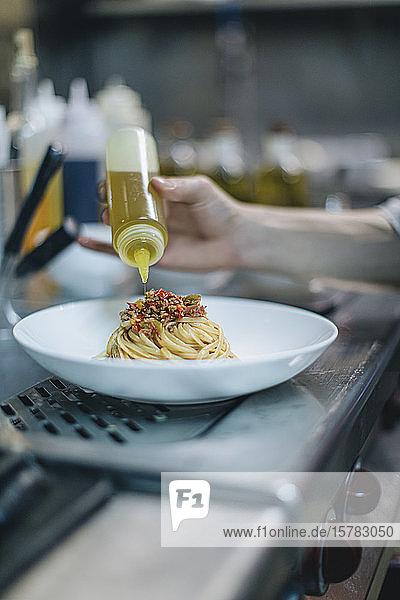 Koch  der ein Gericht in der traditionellen italienischen Restaurantküche zubereitet