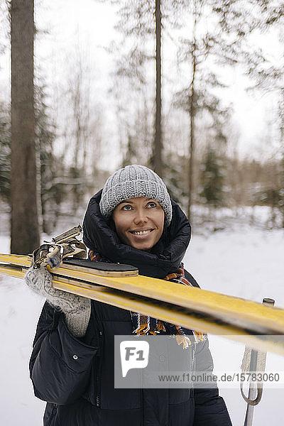 Porträt einer lächelnden Frau mit Skiern im Winterwald