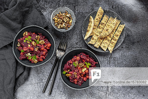 Pita bread and plates of beetroot salad with chick-peas  roasted walnuts and parsley