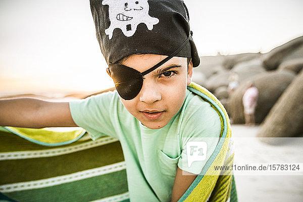 Porträt eines als Pirat verkleideten Jungen am Strand