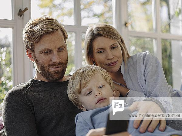 Familie benutzt Mobiltelefon im Wintergarten zu Hause
