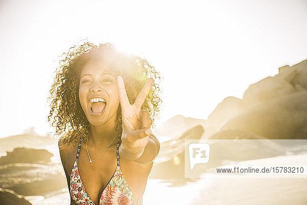 Porträt einer unbekümmerten jungen Frau beim Siegeszeichen am Strand