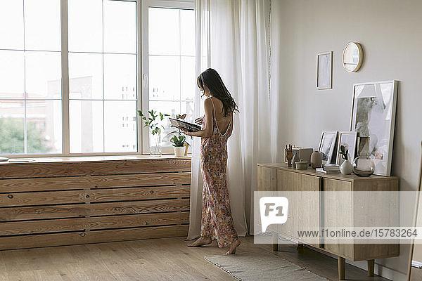 Junge Frau zu Hause am Fenster mit einem Buch in der Hand