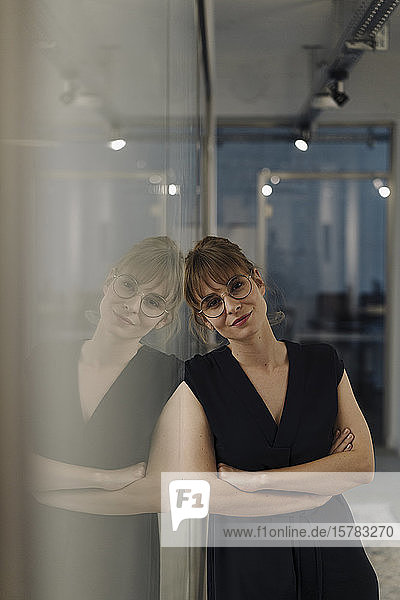Portrait of businesswoman leaning against glass pane in office