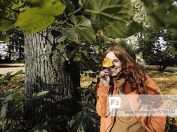 Porträt einer glücklichen rothaarigen Frau mit Herbstblatt