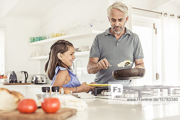 Father making fried egg for daughter at home