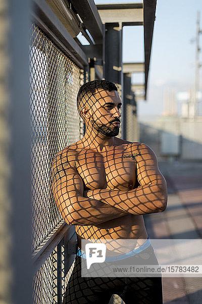 Sportler  der sich auf einen Zaun lehnt und zur Seite schaut