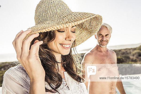 Lächelnde Frau mit Strohhut am Beckenrand