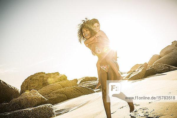 Glückliche Mutter trägt ihren Sohn huckepack am Strand
