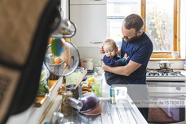 Mann in der Küche  der Essen zubereitet und mit seinem Sohn kuschelt