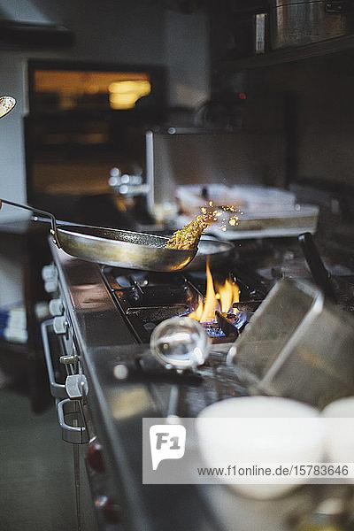 Zubereitung eines Gerichts am Gasherd in der Restaurantküche